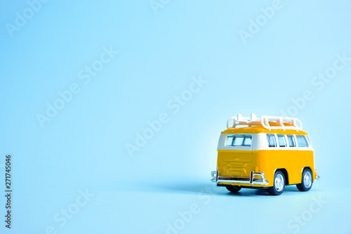 Obraz na plátně  Funny yellow retro car with surfboard on blue background
