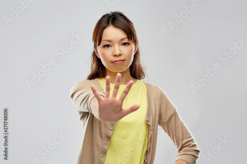 people, prohibition and rejection concept - young asian woman showing stop gesture over grey background - 271748000