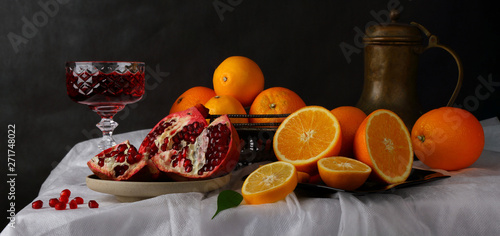Fototapeta Still life with a glass of wine, jug and fruit on a dark background obraz