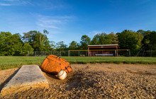 Aseball And Glove On Pitchers Mound On Early Morning Springtime