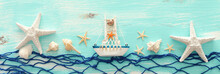 Vacation And Summer Concept With Vintage Boat, Fishnet, Starfish And Seashells Over Pastel Blue Wooden Background. Top View Flat Lay