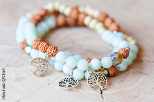 Fotografia Mineral stone amazonite and tree pendant bead bracelet on natural wooden backgro