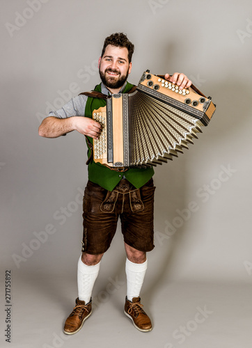 Photo cool young musician with black beard and leather trousers and traditional costum
