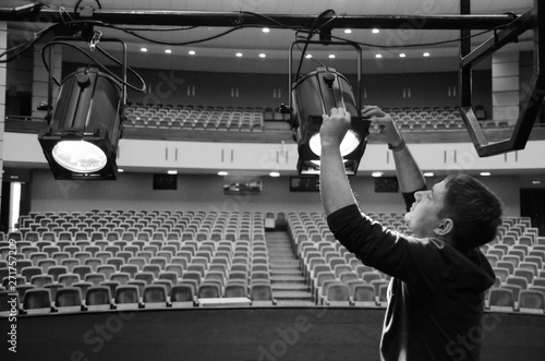 A young guy mounts lighting equipment on the stage of the theater - 271757209