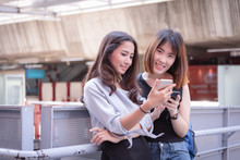 Two Woman Lovely  Friends Using Mobile Phone For  Travel Online Checking  In City