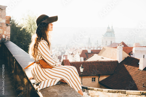 Side view of casual young girl sitting in view point in the Prague centre Tapéta, Fotótapéta