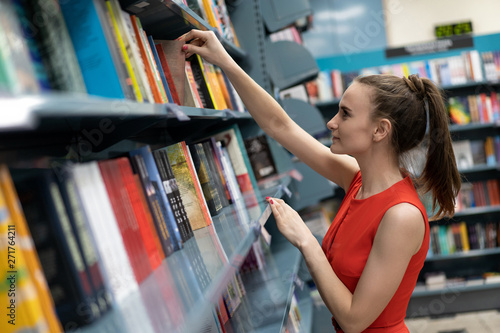 Photo  Beautiful white european girl looking for a book on stilazhah in the library, a bookstore