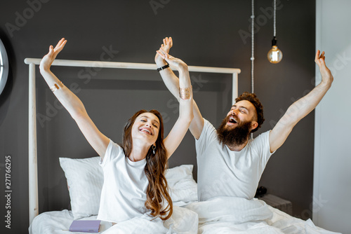 Happy couple waking up with raised hands, feeling good in the morning at home Fototapeta