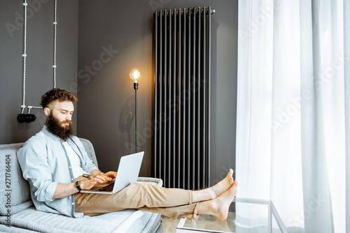 Canvas Prints Textures Creative bearded man working with laptop, sitting on the couch in the living room at home