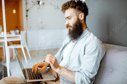 Creative bearded man working with laptop, sitting on the couch in the modern studio apartment