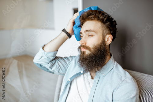 Fototapeta Bearded man with headache applying ice bag while sitting on the couch at home