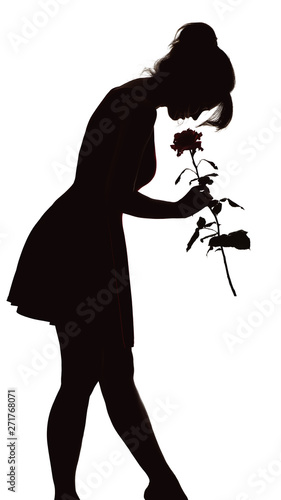 Photographie silhouette of a young elegant woman in a dress tilted his head to the bud of ros