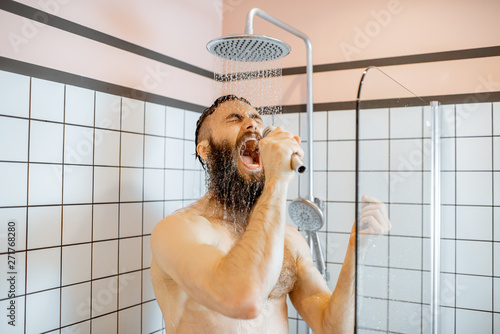 Fototapeta Joyful bearded man singing into the micrphone while taking a shower in the bathr