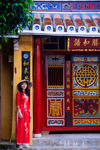 A Young Vietnamese Woman Wearing A Traditional Ao Dai Dress And Standing Outside A Temple In The Historic Town Centre, Hoi An, Vietnam