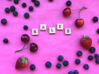 Leinwandbild Motiv Sales concept. Sales - word spelled with letter pieces on pink background with cherries, strawberries, blueberries