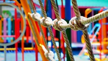 Focus On The Old White Rope Mesh And Blurred Background Of Many Outdoor Play Equipments In Playground At Kindergarten School
