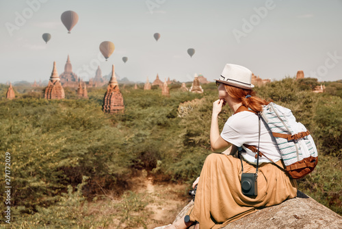 woman traveler with backpack enjoying views of Buddhist stupas and air balloons in the ancient Bagan, Myanmar