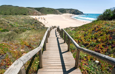 Fototapeta na wymiar Wooden steps to the sunny beach in Portugal town. Ocean waters and green hills over peaceful seaside at sunny day of Algarve area