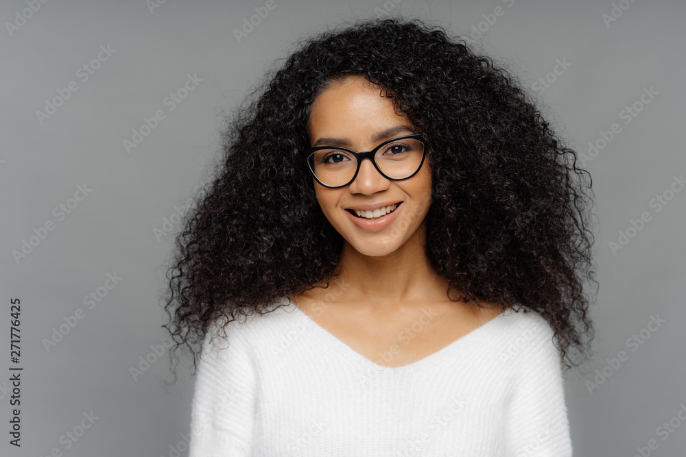 Fototapety, obrazy: Gorgeous lovely curly woman with Afro hairstyle, feels glad, smiles gently at camera, wears optical glasses and white sweater, isolated on grey background. Happy emotions and feelings concept