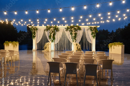 Photo  Night wedding ceremony with arch, orchid flowers, chairs and bulb lights in forest outdoors, copy space
