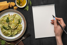 Cropped View Of Woman Writing In Blank Notebook With Pencil Near Served Green Ravioli