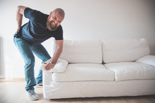 Man Having Backache (low Back Pain) While Moving Or Trying To Lift A Sofa
