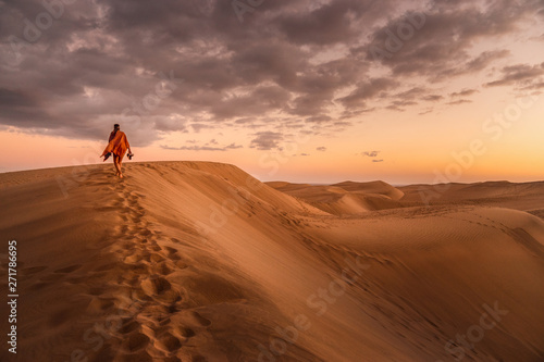 Foto young woman from behind walking in sand dunes of maspalomas, gran canaria