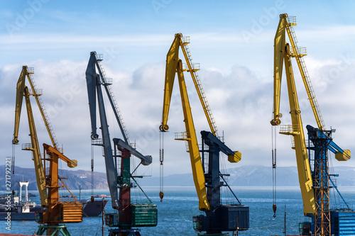 Foto auf AluDibond Schiff View of old port cranes in seaport on shore of ocean