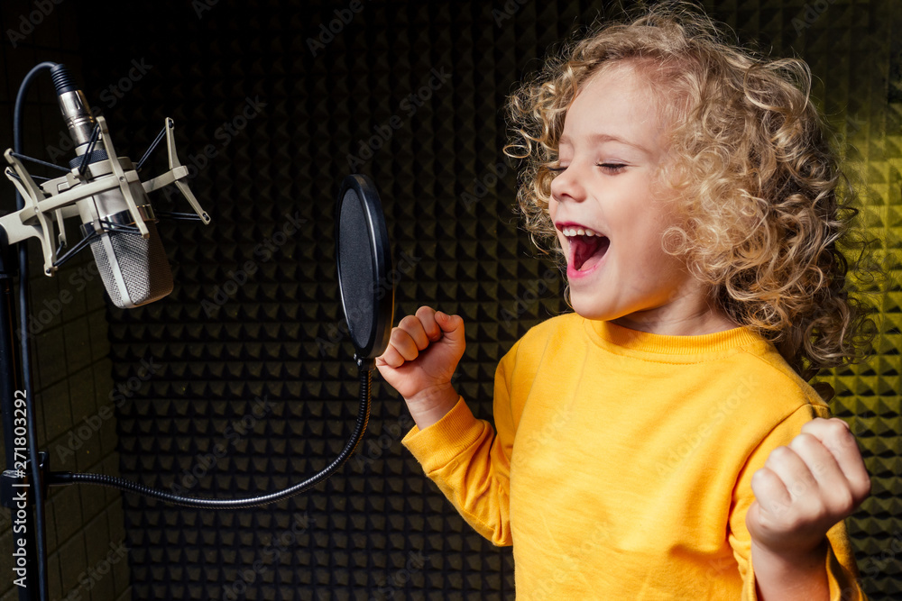 Fototapety, obrazy: girl blonde curly hair style star singer artist in a yellow blouse with headphone recording new song with microphone.
