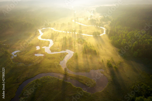 Fototapeta Misty morning river in sunlight. River landscape aerial view. Riverside view from above. Summer nature in sun rays. Drone view on  sunny nature. Scenery river top view. obraz