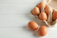 Brown Chicken Eggs In Carton Box On White Background, Space For Text