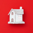 New Year wooden toy house on red paper background. Creative holiday christmas concept. Minimal style.