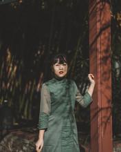 Woman In Green Dress Beside Maroon Post