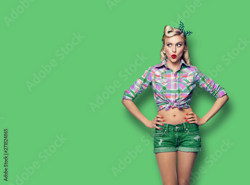 Fotografía  Photo of young surprised woman, looking sideways, dressed in pin-up style, over