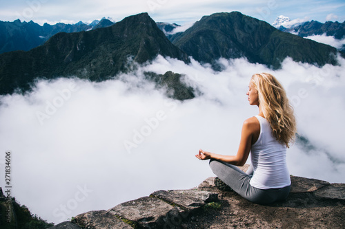 Blonde young woman with blonde hair doing meditation sitting in lotus on edge of rocky hill enjoying relax time of travel.Female tourist doing yoga from high peak mountain enjoying calm of nature