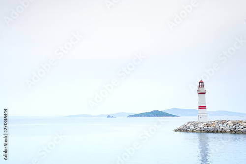 Lonely lighthouse on a stone road in the middle of the sea with views of the mountains and fog, Turgutreis Turkey