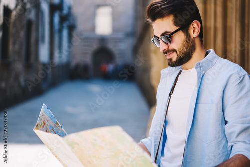 Fotografia  Positive hipster guy checking routes of destinations on map during city tour on