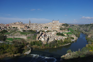 Fototapeta na wymiar City view across the Tagus river to Toledo a medieval city in central spain. It is a popular tourist destination with many historic buildings to explore.