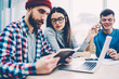 Young clever hipster guy reading literature sitting at desktop near female student in eyeglasses and laptop at university campus while handsome male friend having positive mobile phone conversation .