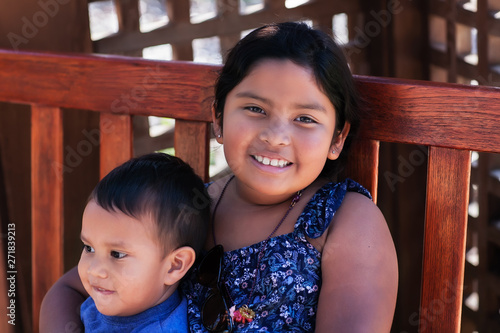 Photo  An older sister holding her younger brother tightly while sitting on a wooden bench