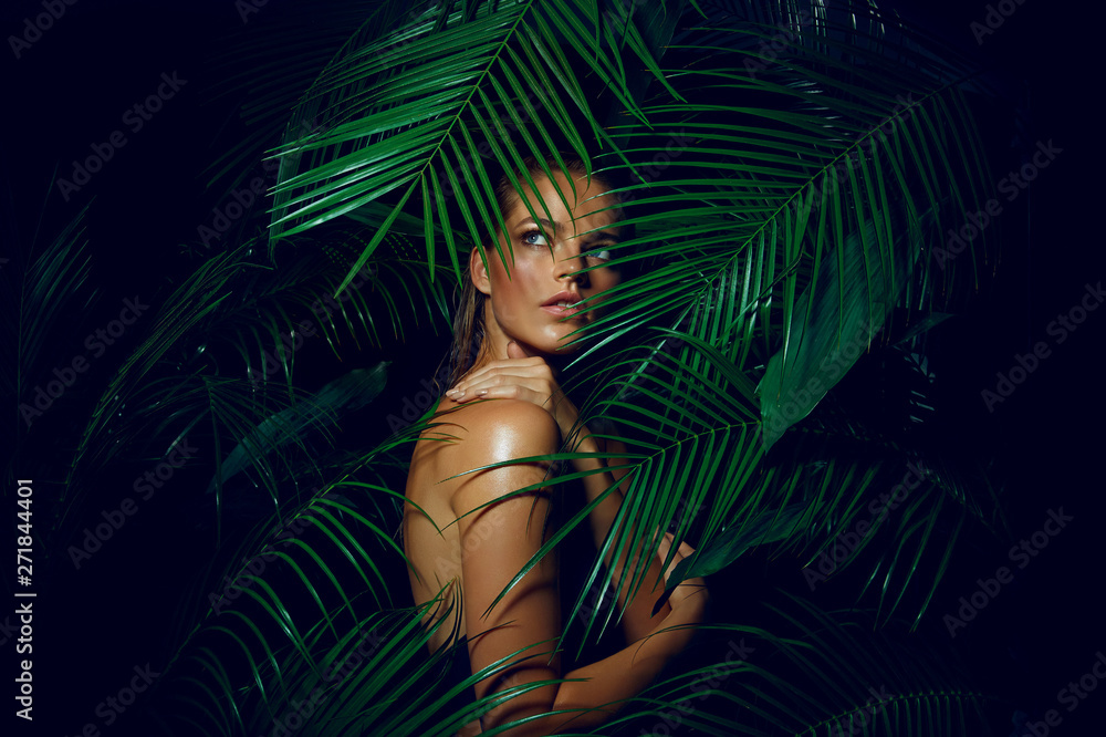 Fototapety, obrazy: A beautiful tanned girl with natural make-up and wet hair stands in the jungle among exotic plants
