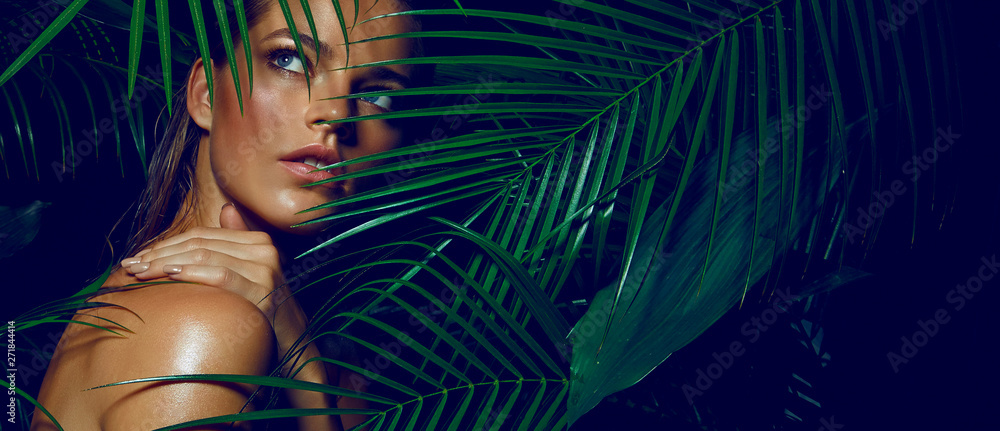 Fototapeta A beautiful tanned girl with natural make-up and wet hair stands in the jungle among exotic plants