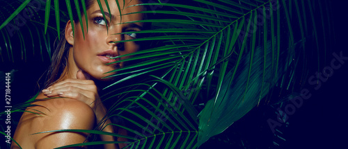 Fototapeta A beautiful tanned girl with natural make-up and wet hair stands in the jungle among exotic plants obraz