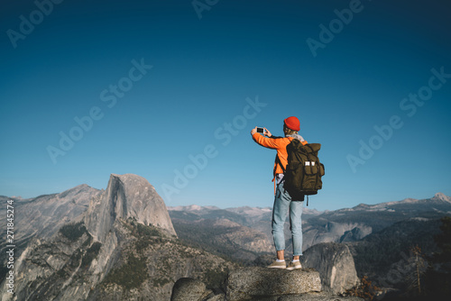 Back view of female blogger taking selfie on smartphone on hiking tour discover wild lands on vacation, girl wanderlust using telephone for making photo standing on rock cliff breathtaking scenery Canvas Print