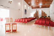 Modern Catholic Church Hall With Red Chairs And Organ On Background.