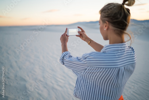 Back view of young woman tourist making selfie on smartphone camera exploring wh Wallpaper Mural