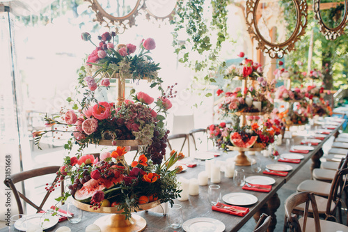 Fotografering  Wedding table flowers with fruits and berries decor in red white pink green colors