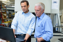 Two Management Level Workers Looking At Laptop In Factory