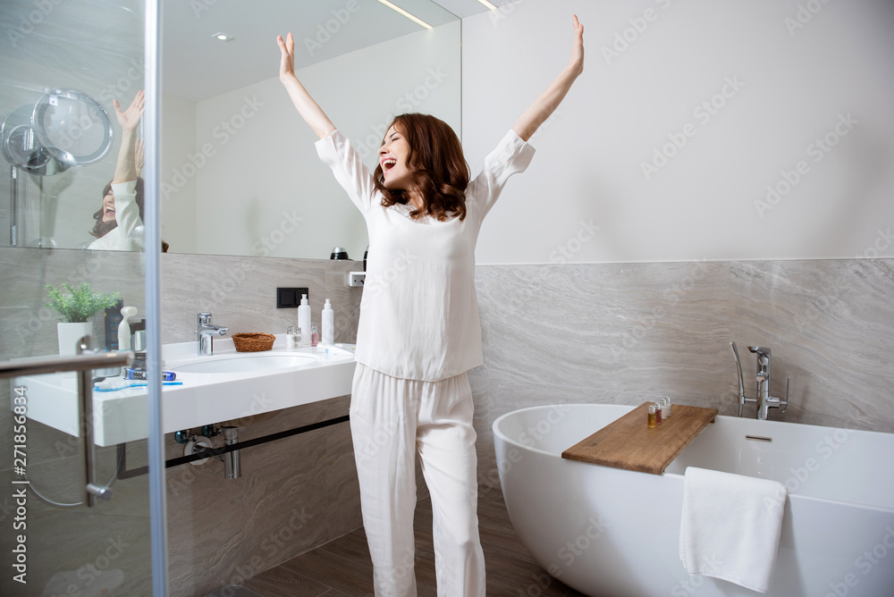 Fototapety, obrazy: Excited woman greeting morning in the bathroom and putting hands up