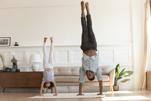 Active African Kid Girl Copy Father Doing Handstand At Home